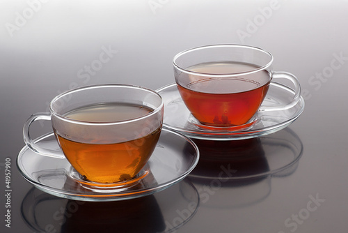 Transparent cup with green and black tea