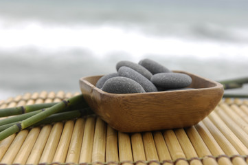 Stones in wooden bowl and bamboo grove on mat , zen concept