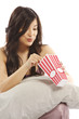 Young asian woman holding pillow eating popcorn