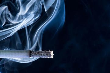 Burning cigarette with smoke on black background
