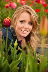 Dutch blond girl in field with tulips