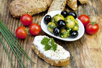 Grüne Oliven mit frischem Brot und Kräutern auf Holzbrett
