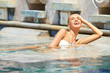 Beautiful blonde girl relaxing in the pool