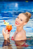 Happy blonde holding a drink while in a pool