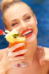 Glamorous woman enjoying a tropical cocktail