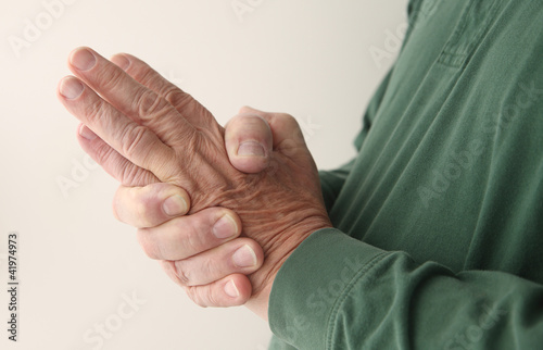 man tries to massage the numbness out of his hand