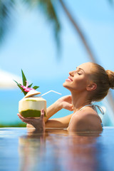Woman relaxing in pool with a cocktail