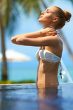 Pretty girl massaging her neck after a swim