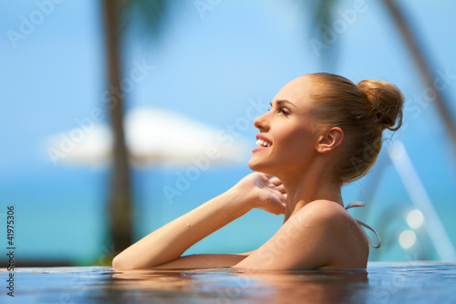 Lovely blonde girl chest deep in a pool