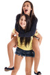 Preteen and teen sisters on piggyback isolated on white