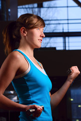 beautiful woman is exersising in gym at evening