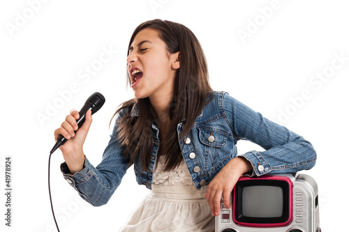 Preteen girl singing karaoke with microphone isolated on white