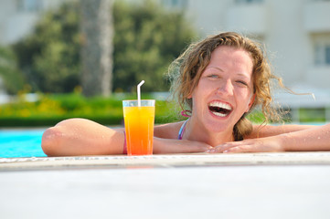 attractive woman is smiling from swimming pool in resort