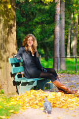young woman is sitting on the bench in autumn park and looking a