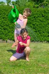 Kinder spielem mit Gießkanne