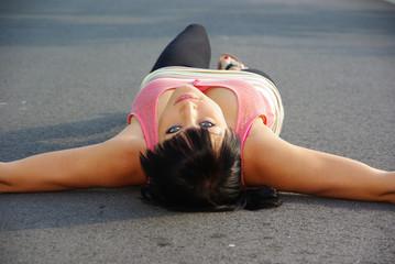 Frau liegt auf einer Straße
