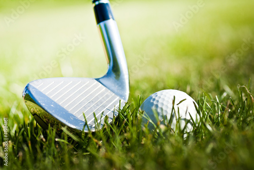 golf club and golf ball in green grass