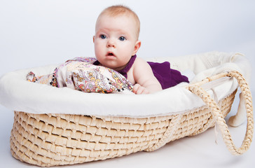 little sweet girl a baby lying on a beautiful cushion in a wicke
