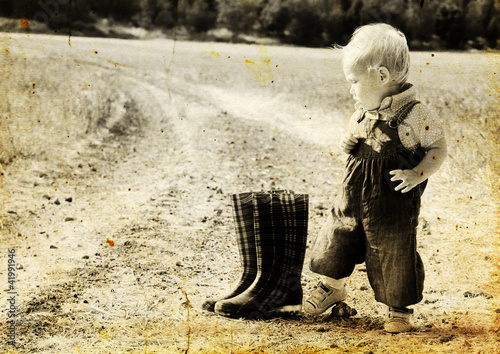 kid  in harvested field. Photo in old image style.
