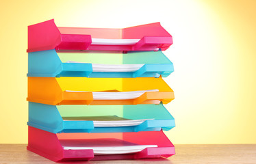 bright paper trays on wooden table on yellow background