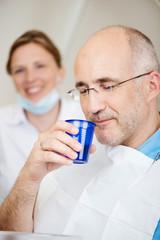 patient beim zahnarzt mit einem becher wasser