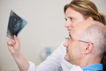 zahnärztin zeigt ein röntgenbild