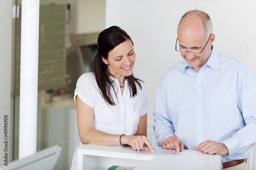 arzthelferin und patient an der rezeption