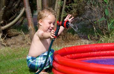 Kleiner Junge spielt mit Wasser am Planschbecken