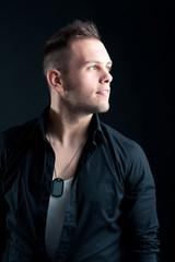 Confident man portrait against black background.
