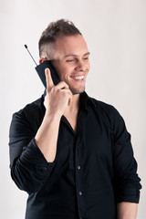 Happy man talking at the phone against white background.