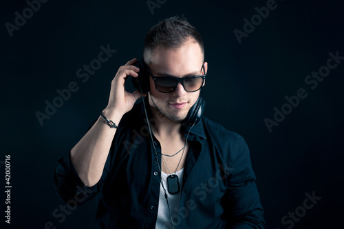 Portrait of man with ear-phones on black background.