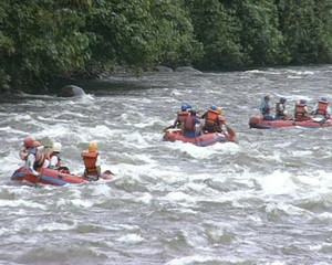 People in rubber boats sail down wildwater river