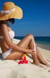 Woman applying sunscreen on the beach