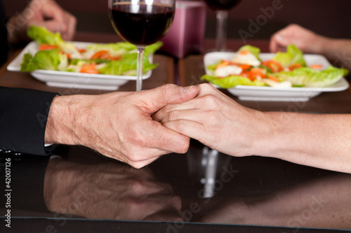 Touching hands at romantic dinner in restaurant