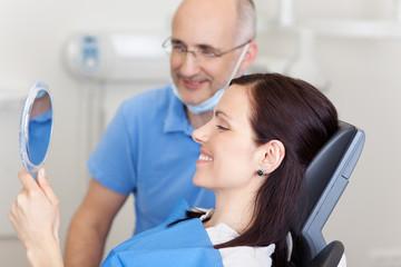 frau beim zahnarzt schaut in den spiegel