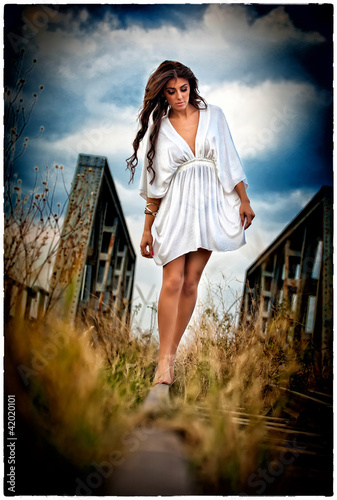 a sensual walking girl with white dress on the railway