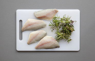 Fish with herbs on the chopping board