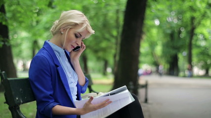 Businesswoman with documents and cellphone in the park