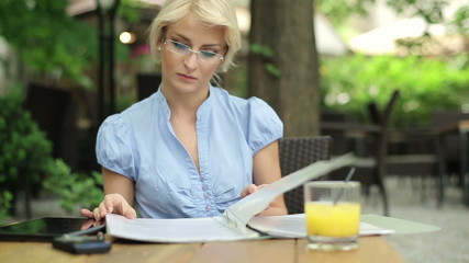 Businesswoman overwhelmed by too much paperwork in cafe