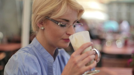 Happy businesswoman drinking coffee in cafe, steadicam shot