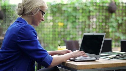 Businesswoman working on laptop and drinking juice in cafe