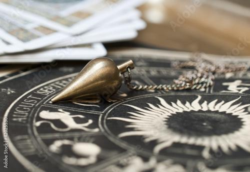 Pendel mit astrologischer Karte und Tarotkarten