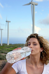 Woman drinking water near wind turbines
