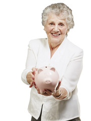 portrait of senior woman showing a piggy bank over white backgro