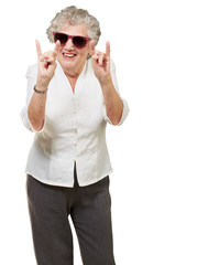 portrait of a happy senior woman doing rock symbol over white ba