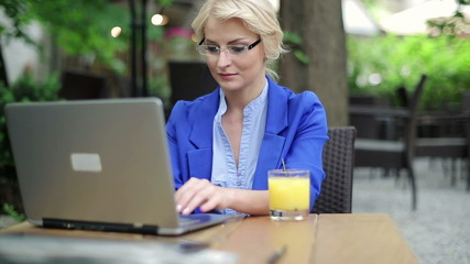 Happy businesswoman finishing work on laptop in cafe
