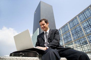 Businessman using his laptop in the city