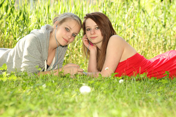 young teenager girls sharing music on a meadow