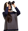 portrait of young girl looking through a binoculars over white