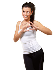 portrait of young healthy girl gesturing heart symbol over white